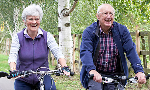 An older couple, a man and a woman, ride bikes alongside one another