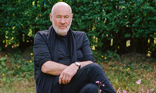 Musician Fish, wearing all black, sat in a garden.