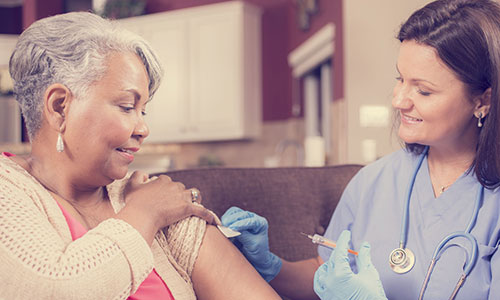 Nurse giving flu jab to woman