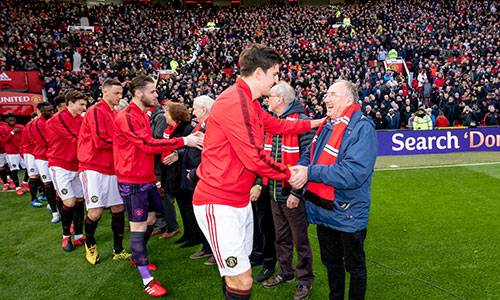 Manchester United players shake holds with older people on the pitch at Old Trafford