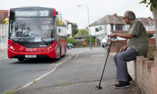 Older man sitting on a wall, holding his walking stick waiting for the bus to arrive