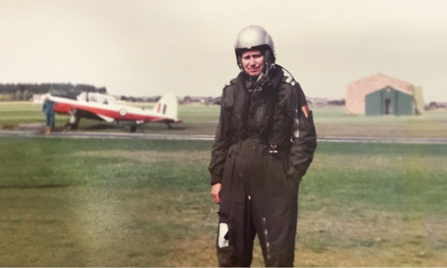 Old photo of an RAF pilot in full kit and standing in front of a plane.