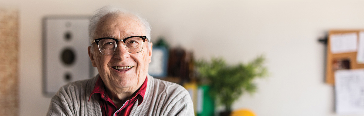 A older man wearing glasses stands in his home, smiling brightly
