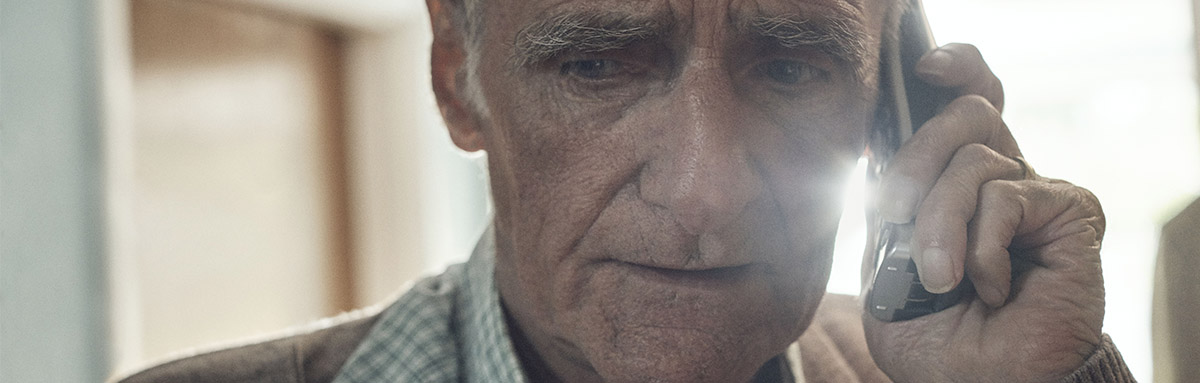 An older man speaks worriedly on the phone to Age UK