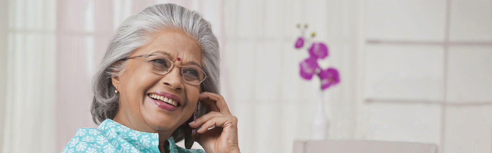 An older woman talks on the phone, smiling