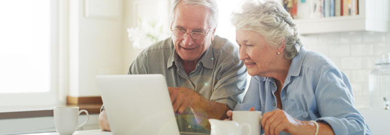 Couple looking at a laptop and smiling