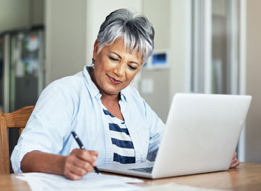 Woman on laptop making notes