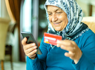 Woman on smartphone holding bank card whilst transferring money