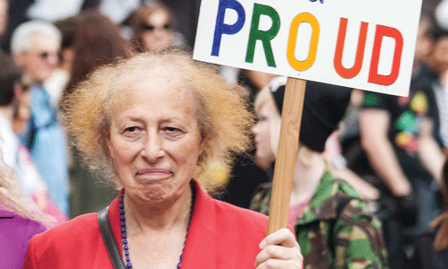 woman holding sign that says proud in colourful writing on it