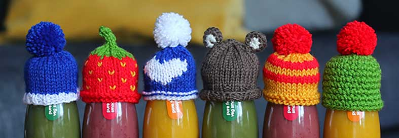 Knitted hats on innocent smoothie bottles