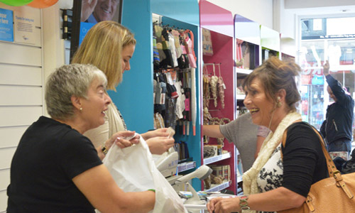 A woman donates items at her Age UK shop